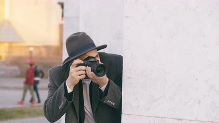 kgb : Young male spy agent wearing hat and coat photographing criminal people and hiding behind the wall Stock Footage