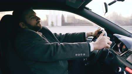 sıkıntı : Young bearded business man sitting in car very upset and stressed after hard failure and moving in traffic jam