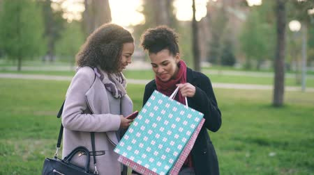 smíšené rasy osoba : Two attractive mixed race women surpisely have meeting in the park near mall store