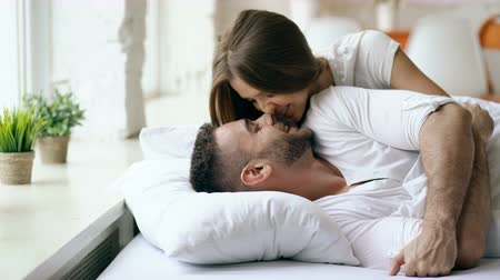 проснуться : Young beautiful and loving couple wake up at the morning. Attractive woman kiss and hug his husband in bed