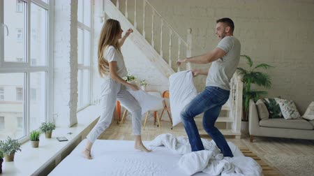 kavga : Young happy and loving couple having pillow fight in bed at home Stok Video