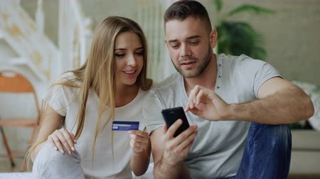 nákupy : Attractive young couple with smartphone and credit card shopping on the internet sit on bed at home
