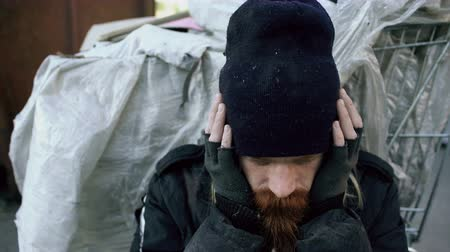 sacked : Closeup of young bearded homeless man sitting near shopping cart upet and stressed alone in the street