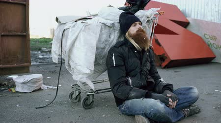 sacked : Young bearded homeless man sitting on a sidewalk near shopping cart ang garbage container during cold winter day
