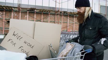 sacked : Dolly shot of Bearded homeless man walking down the street with shooping card at cold autumn day Stock Footage