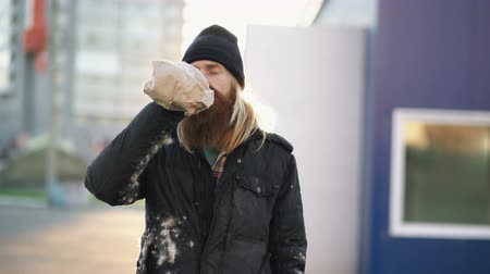 hívó : Portrait of Drunk homeless man with drink alcohol from paper bag while standing on the city street and looking at camera