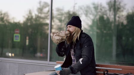 hobo : Very drunk homeless man talking to people walking near him and beg for money while sitting on bench at the sidewalk Stock Footage
