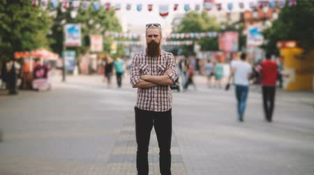 time flow : Zoom in timelapse of Young bearded man standing still at sidewalk in crowd traffic with people moving fast Stock Footage