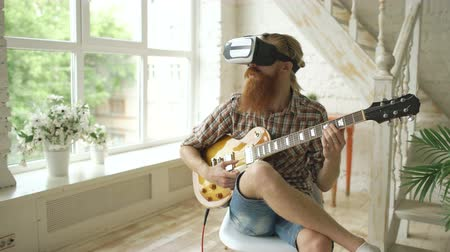 zkušenost : Young bearded man sitting on chair learning to play guitar using VR 360 headset and feels him guitarist at concert at home