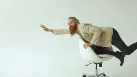 humor : Slowmotion of Bearded funny businessman have fun riding on office chair on white background