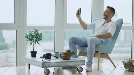 erkély : Young happy man have online video chat using digital tablet computer sitting on balcony in modern loft apartment