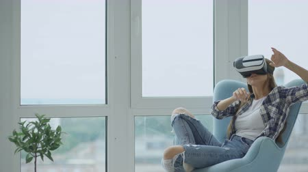 fejhallgató : Young woman have VR experience using virtual reality headset sitting in chair on balcony Stock mozgókép