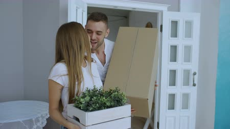 Войти : Young happy couple walking into new house after moving day and kiss each other