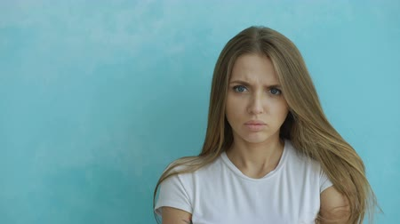 сердитый : Portrait of angry young woman looking into camera nervous on blue background Стоковые видеозаписи