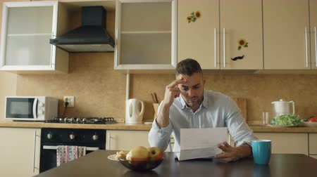 adósság : Uspet young man reading letter with unpaid bill in the kitchen at home Stock mozgókép