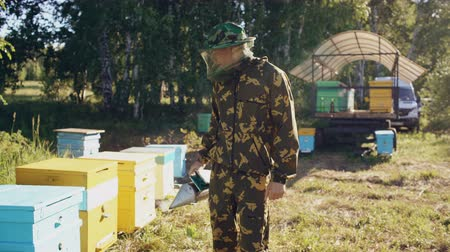 apiary : Stedicam shot of Young beekeeper man smoking bees away from beehive in apiary