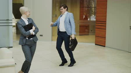 выражающий : Crazy businessman dancing with briefcase in modern lobby while his colleagues walking and watching him surprised
