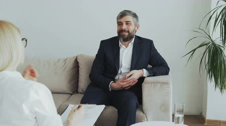 psychotherapist : Smiling businessman sitting on couch talking to female psychologist in office