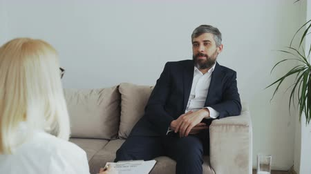 psychotherapist : Adult businessman sitting on couch talking to female psychotherapist in office Stock Footage