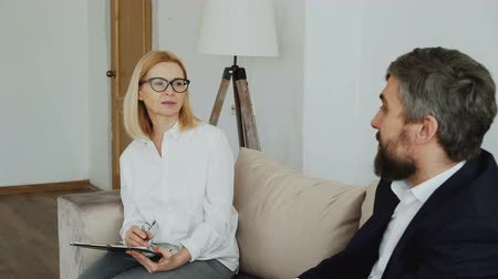 psychotherapist : Female experienced psychiatrist listening to depressed businessman patient in her office Stock Footage