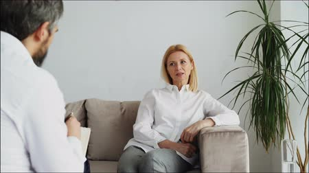 psychotherapist : Male psychoanalyst listening adult female patient and writing notes in psychologist office Stock Footage