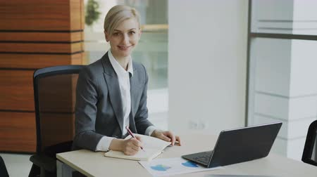 cadeira : Portrait of Attractive blonde businesswoman sitting at table writing in notebook smiling into camera in modern office