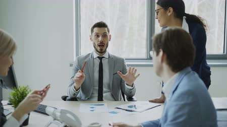 workgroup : Businessman discussing future business project with male and female colleagues sitting at the table in modern office