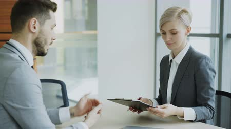 договориться : Male colleague giving contract for signing to blonde businesswoman in suit and discussing details in modern office