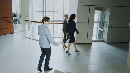 előcsarnok : Businessmen and busineswoman colleagues walking and meet in modern office center indoors
