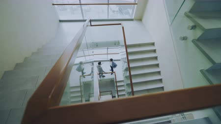 előcsarnok : Top view of two businessmen meet at stairs in modern office center and talking while having break Stock mozgókép