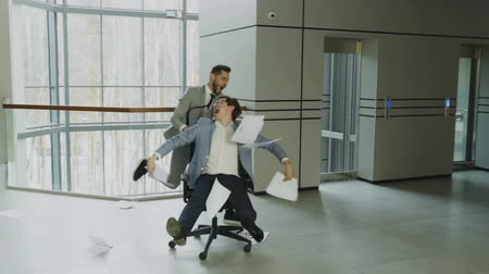 két : Slow motion of Two crazy businessmen riding office chair and throwing papers up while having fun in lobby of modern business center