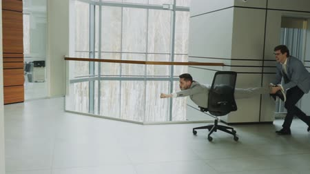 boss : Slow motion pan shot of two funny businessmen riding office chair while having fun in lobby of modern business center