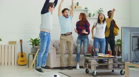 watch tv : Happy young friends watching sports game on TV jumping and celebrating victory of favourite team at home Stock Footage