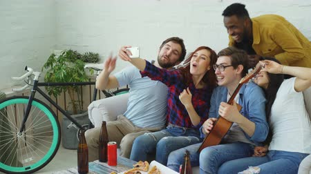 cheers : Happy student friends taking selfie on smartphone camera and posing while have home party in shared accommodation indoors