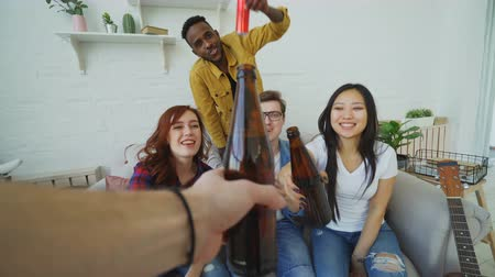 cheers : Point of view shot of male hand clinking beer bottle with friends while celebrating party at home indoors Stock Footage
