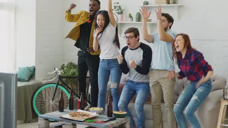leaping : Slow motion of multi ethnic group of friends sports fans watching sport match on TV together jumping and cheering up new goal at home