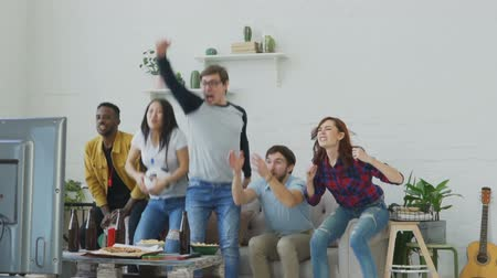 вентилятор : Slow motion of multi ethnic group of friends sports fans watching sport match on TV together jumping and cheering up new goal at home