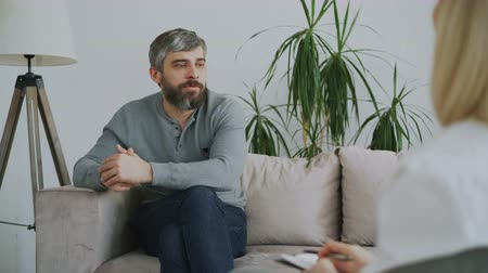 értékelés : Adult bearded man talking about his problems to psychologist in her office indoors