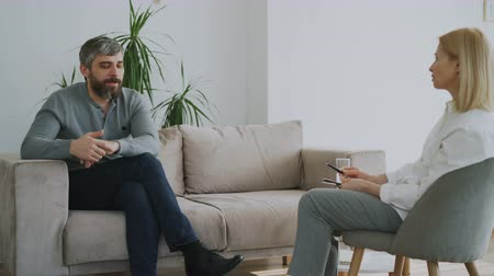counselling : Adult bearded man talking about his problems to psychologist in her office indoors