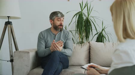 psychotherapist : Depressed man talking about his porblems with female psychologist