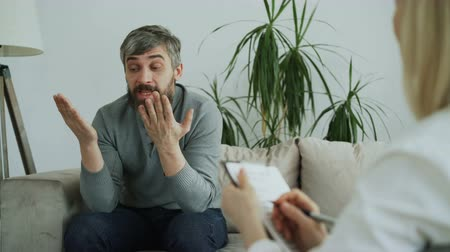 psychotherapist : Angry man talking about his family porblems with female psychologist in her office indoors Stock Footage