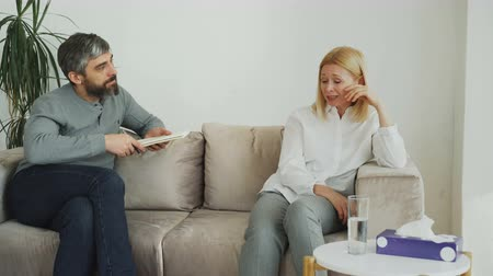 cheerless : Male experienced psychologist talking and calm down depressed crying woman patient during psychotherapy session Stock Footage