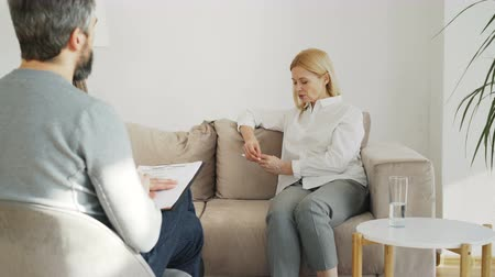 psychotherapist : Adult stressed woman with depression talking with male professional psychoanalyst in psychotherapy office indoors
