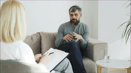 escrever : Stressed bearded man talking about his problems to psychologist in her office indoors