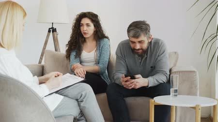psychotherapist : Female professional psychologist listening and writing notes while young woman arguing and her boyfriend surfing in smartphone during visit psychotherapy office indoors