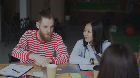 conference table : Young hipser man in talking about new start-up project with female and male multi ethnic team in loft office indoors Stock Footage