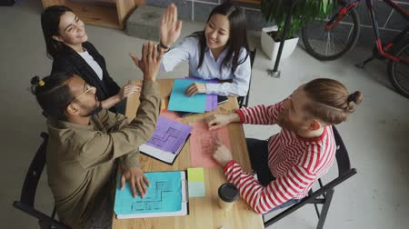 давать : Top view of start-up business team of multi-ethnic coworkers giving high five all together sitting at table in office