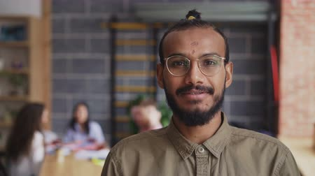 kezdet : Young african american male entrepreneur in shirt and glasses smiling and looking at camera while his colleagues working in modern office indoors Stock mozgókép