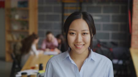 lider : Portrait of asian confident businesswoman looking at camera and smiling while her multi-ethnic team working on start-up project in modern loft office Stok Video