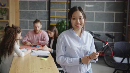 munkatársa : Portrait of young asian female entrepreneur holding digital tablet looks at camera and smiling on busy start-up office background